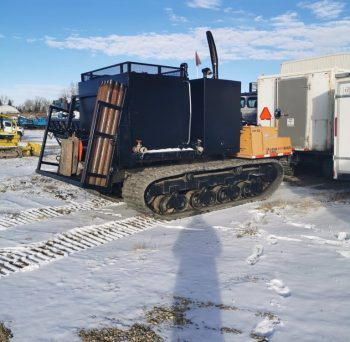 Morooka MST 800VD with attached support equipment. Unit is capable of hauling various supplies and support equipment to remote drill sites. Pictured with 6m3 of heated water storage.